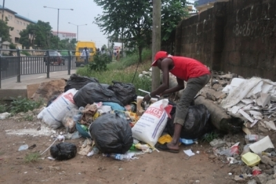 Daily life in Nigeria after coronavirus lockdown relaxation: a scavenger picks scrap in Lagos. Press Association