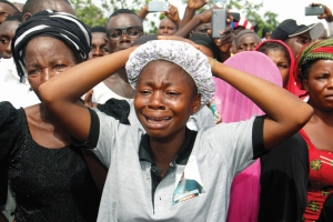 Relatives cry as they mourn during a funeral service for 17 worshippers and two priests, who were allegedly killed by Fulani herdsmen