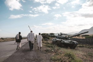 People walk next to an abandoned tank belonging to Tigrayan forces south of the town of Mehoni, Ethiopia