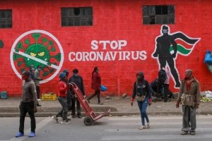 Kenyans walk past a mural about the coronavirus, Haile Selassie Avenue, Nairobi. Press Association