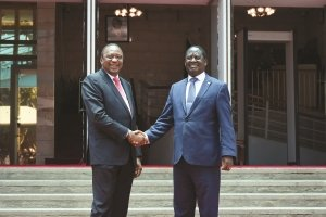 Kenyatta (left( and Odinga shake hands after their reconciliation talks