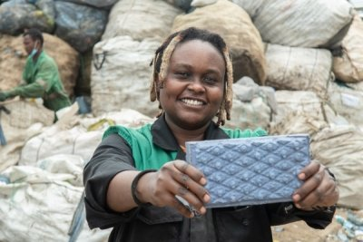 Nzambi poses with one of the recycled plastic blocks.